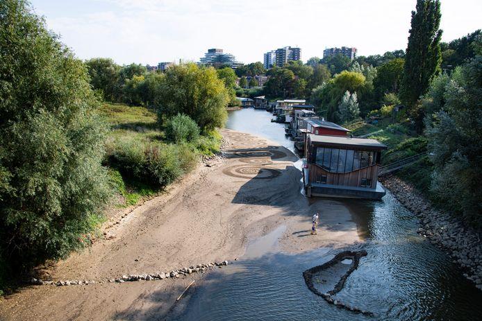 Een scheve woonboot in het lage water van de uitloop van Het Meertje in de Waal bij Nijmegen.