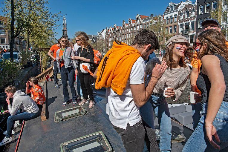Koningsdag in Amsterdam: dansen en drinken op een boot in de Prinsengracht. Volgens de GGD zijn die dag in de stad zeker 483 mensen besmet geraakt, nog afgezien van degenen die niet door de GGD zijn getest.  Beeld Guus Dubbelman / de Volkskrant