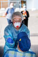 Medewerkers van de GGD nemen een keel- en neusmonster af bij mensen in de mobiele teststraat in Bergen op Zoom.