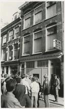 Buurtbewoners kijken in de Herenstraat toe terwijl de politie een inval doet in koffiebar Ria Gran, waar boven gelegenheid tot roulette spelen werd gegeven.