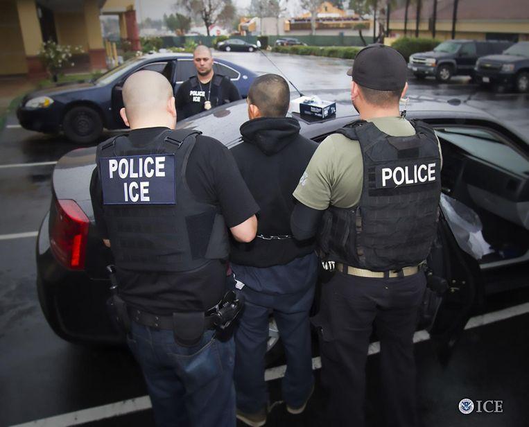 Politie-agenten van de ICE arresteren een vermeende illegale immigrant. Beeld afp
