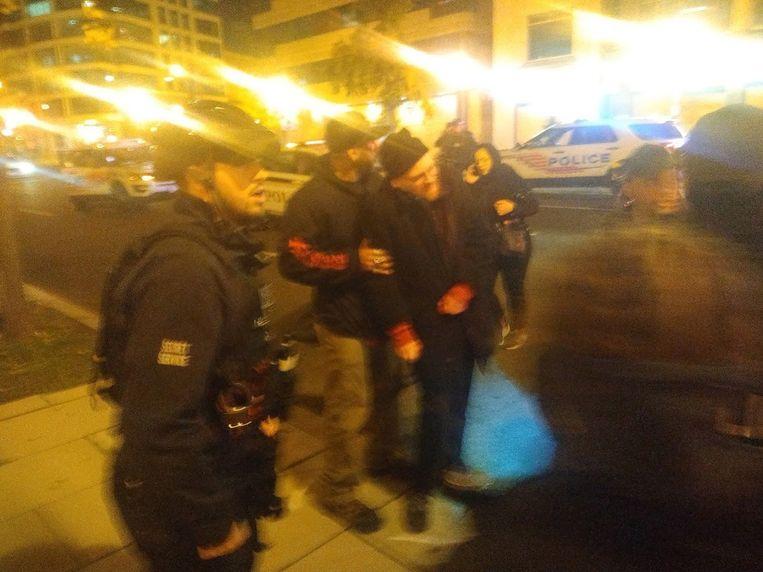 Een Proud Boy met een gewonde man, dinsdagnacht in Washington.  Beeld Michael Persson