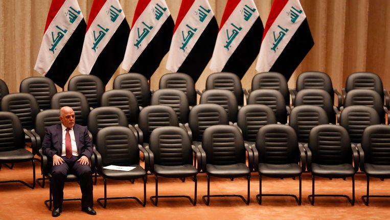 De Iraakse premier Abadi met op de achtergrond Iraakse vlaggen. Beeld REUTERS