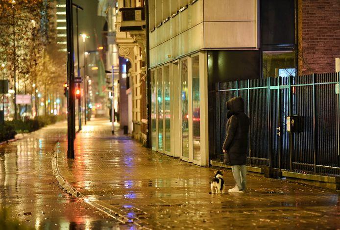 Een vrouw laat haar hond uit in een verder leeg centrum.