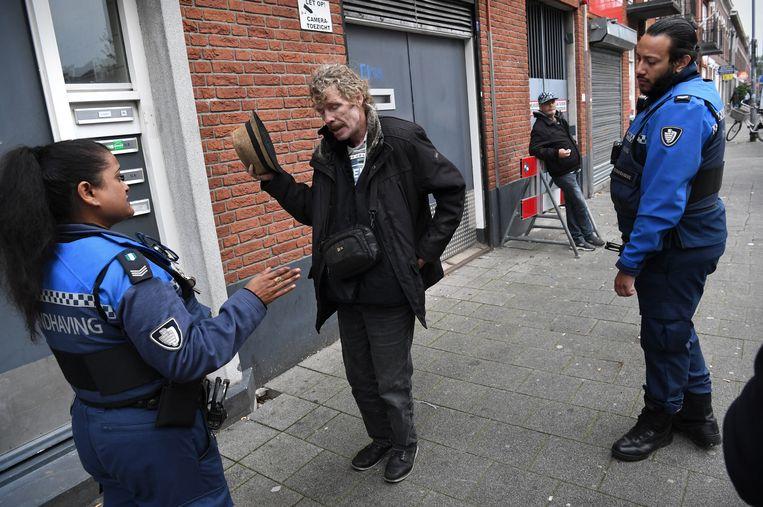 Een man op straat wordt gevraagd niet meer te bedelen.  Beeld Marcel van den Bergh / de Volkskrant