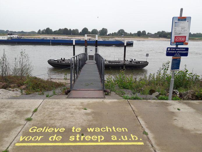 Na de coronabeperkingen dreigt de lage waterstand in de Waal, zoals hier bij de aanlegsteiger Beuningen, de fiets- en voetpontjes dwars te zitten.