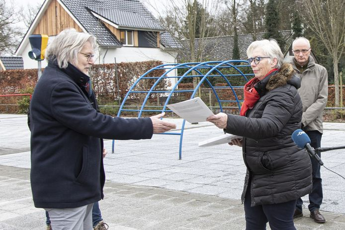 Janny Vokkert overhandigt namens werkgroep Energietransitie Egede-Hancate-Eelen en Rhaan (ET EHER) de plannen van de buurtschappen aan wethouder Henk Nijhof op het plein van basisschool Jan Barbier.