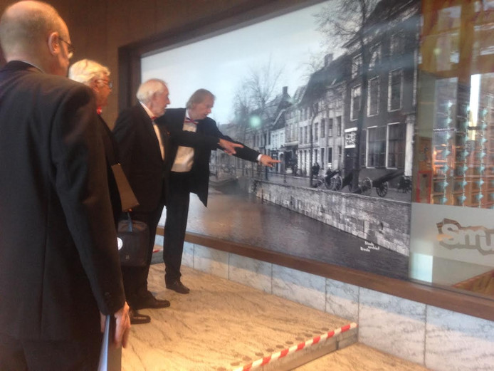 Leden van het mannenkoor bekijken een foto van de oude Haven