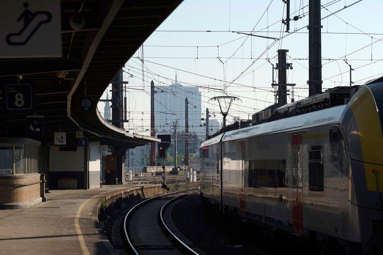 Een trein rijdt een Brussels station binnen.