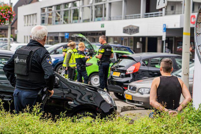 Agenten doorzochten de auto, terwijl een van de vrienden geboeid toekeek.