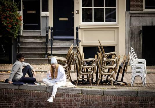 Mensen lunchen bij een stapel stoelen van een gesloten terras van een horecazaak. Horeca moeten voorlopig dichtblijven.