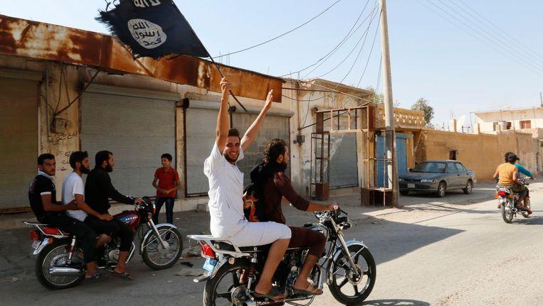 IS-aanhangers rijden met brommers door Tabqa. Beeld REUTERS