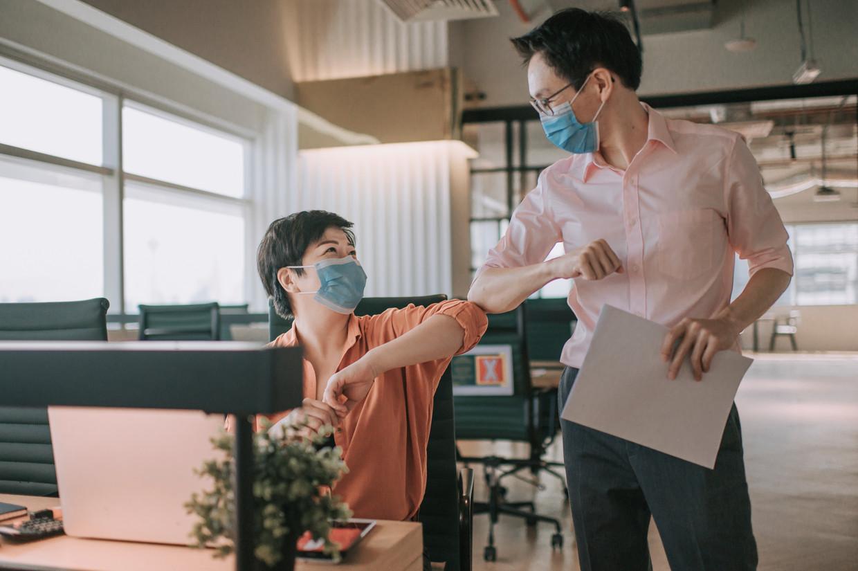 Collega's die elkaar, met mondmasker, coronaveilig begroeten: zal dat een blijver blijken?  Beeld Getty Images