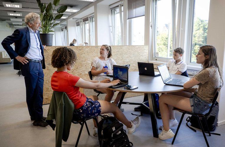 Leerlingen in de klas zijn in gesprek met Paul Rosenmöller, voorzitter van de VO-raad (L), bij het Haags Montessori Lyceum. Beeld ANP
