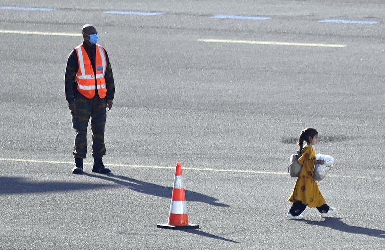 Een meisje uit Afghanistan loopt na aankomst op een vliegveld in België richting de bus die haar verder brengt naar haar verblijflocatie.   Beeld BELGA