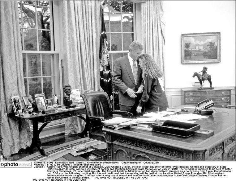 Voormalig president Bill Clinton geeft vaderlijk advies aan zijn dochter na een lange school- en werkdag in the Oval Office (1993). Beeld Photo News