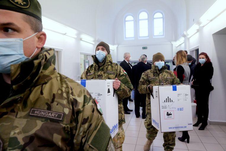 Hongaarse soldaten brengen eind december de eerste vaccins van Pfizer-BioNTech naar het Del-Pest ziekenhuis in Boedapest. Beeld REUTERS