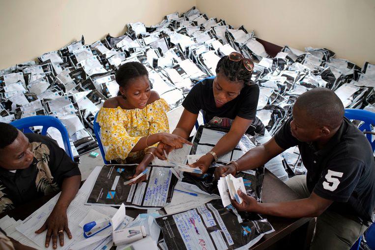 ► Leden van de onafhankelijke kiescommissie tellen stemmen die werden uitgebracht in de Congolese hoofdstad Kinshasa. Beeld AP