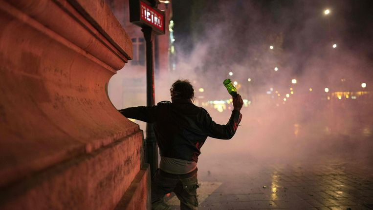 Een demonstrant gooit met een fles richting de politie. Beeld Afp