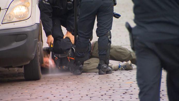 Een betoger werd met traangas in het gezicht gespoten terwijl hij geboeid op de grond lag.