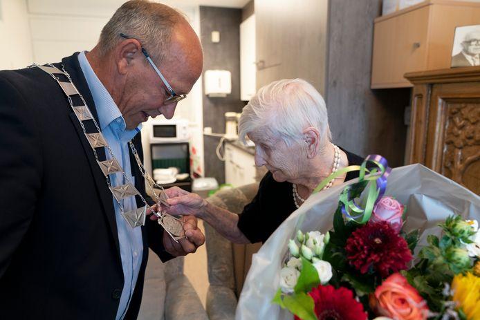 De 100-jarige mevrouw Kuijs van-Opzeeland voelde even aan de ketting van locoburgemeester Kees van Bokhoven.