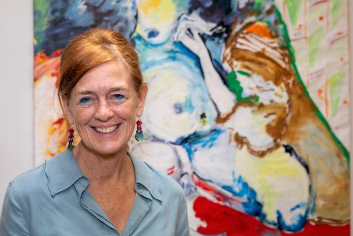 Lieke Jansen van de maatschappelijke opvang SMO in Breda poseert voor een schilderij van een van de kunstzinnige cliënten.