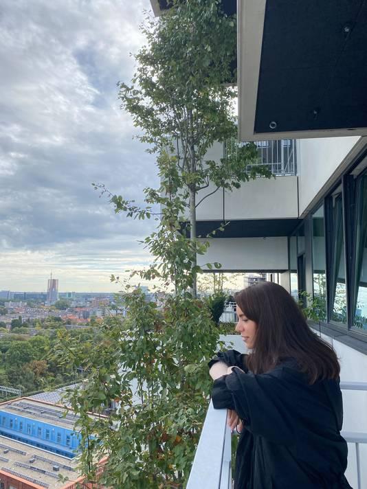 Hale Yesilyurt op haar balkon in het appartement in de groene Trudo Toren op Strijp-S in Eindhoven.