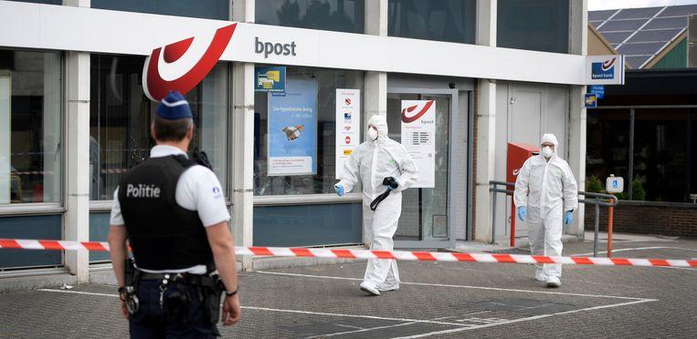 Politie-inspecteurs zoeken naar sporen na een plofkraak in Lommel. Beeld BELGA