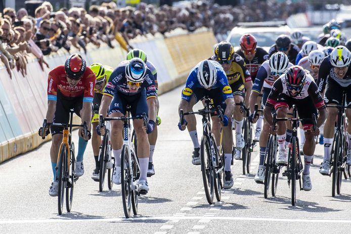 Tim Merlier (m) wint de eerste etappe van de Benelux Tour. Mocht de Belg woensdag in Hoogerheide weer als eerste zijn wiel over de streep drukken, dan smaakt hij  letterlijk het zoet der overwinning.