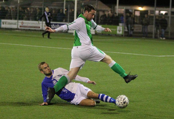 Stijn Obdeijn van Warnsveldse Boys ontwijkt een tackle van Sven Calot van AZC.