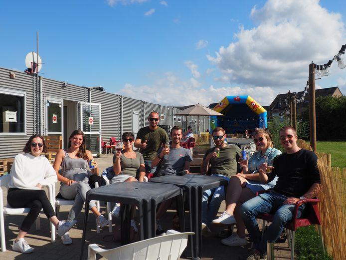Lennert Foqué (vierde van links) klinkt met een aantal bezoekers op het zomerterras van FC Blaasveld.