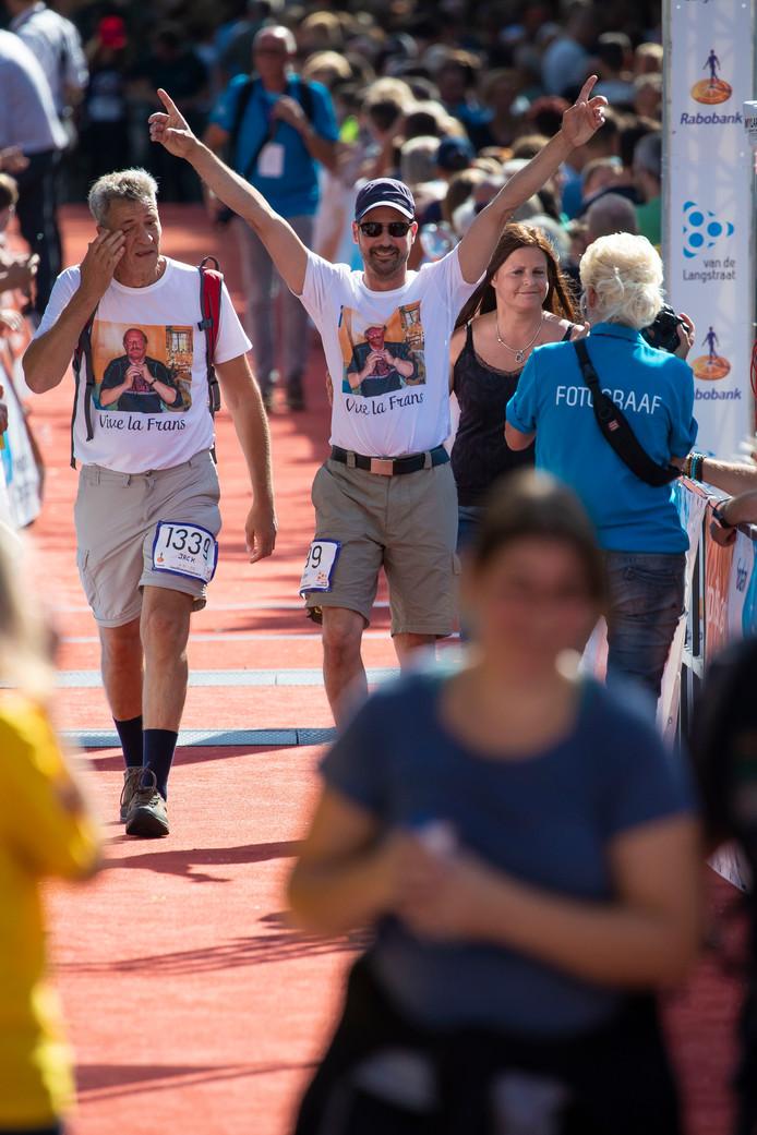 Rogier Oosterbaan juicht na het bereiken van de finish. Links Jack, de vriend van zijn overleden vader. Rechts zijn zus Bianca.