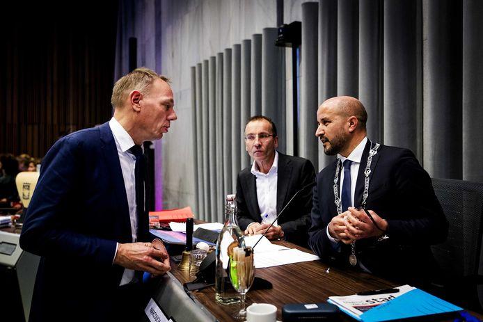 Overleg tussen wethouder Ron König (links) en burgemeester Ahmed Marcouch tijdens het raadsdebat over de Arnhemse bestuurscultuur. In het midden griffier Jozef Kersten.