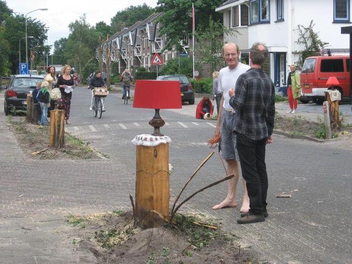 Buren en straatbewoners maken er in de Wilhelminalaan in Harderwijk het beste van nadat de bomen in de straat op verschillende hoogten zijn gecoupeerd en gespleten. foto Marjan Deurloo