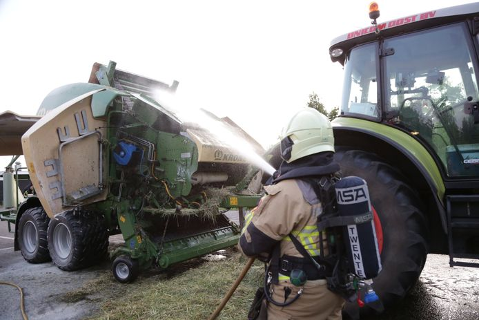 Een brandweerman blust de balenpers.