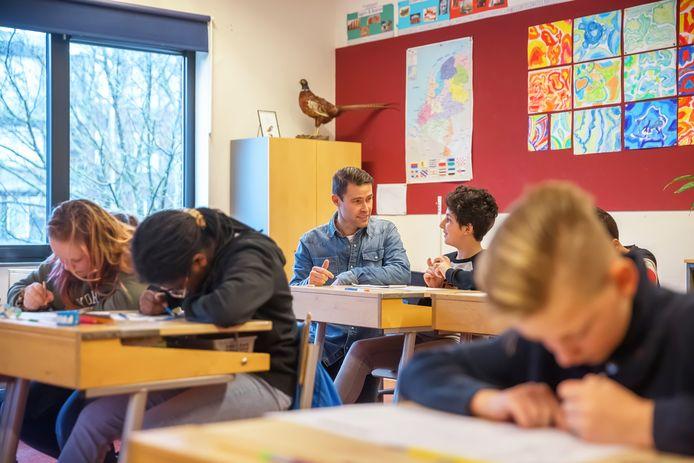 Leerkracht Roland Bierkens (achter) van basisschool Het Palet geeft zijn leerlingen van groep 8 tijdens de hele coronaperiode gewoon les in de klas. 'Dat gaat uitstekend. Ze zijn zelfs fitter dan anders.'