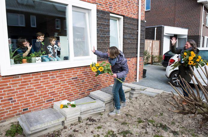 Leerkrachten van basisschool De Brug gaan langs 85 woningen van ouders die hun kinderen thuis moeten houden om zonnebloemen uit te delen.