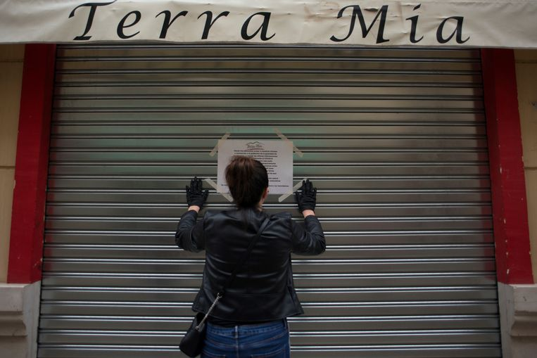 Een vrouw hangt een brief op: de bar blijft de komende tijd gesloten. Beeld AFP