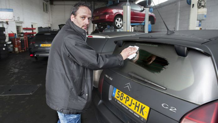 Mario Anderson, chef werkplaats bij Van Oord toont de vette aanslag van gesmolten bitumen op de auto's, die daardoor total-loss zijn geraakt.