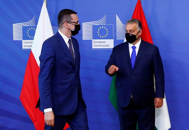 De Hongaarse premier Orbán (rechts) en zijn Poolse collega Morawieck. Beide landen weigeren de Europese meerjarenbegroting  en het coronaherstelfonds goed te keuren.  Beeld Reuters