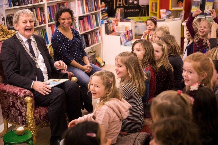 De burgemeester, vader van vijf kinderen, weet wel hoe hij voor moet lezen. Hier op de Nationale Voorleesdag in een boekwinkel, 2016. Beeld Maarten Brante