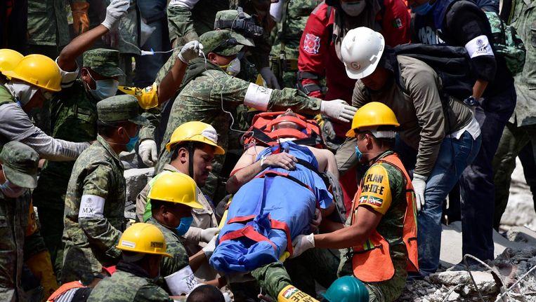 Een man wordt levend uit het puin gehaald. Beeld AFP