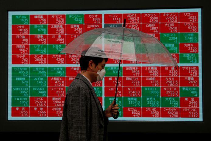 Een man loopt met een mondkapje langs beursresultaten in Japan.