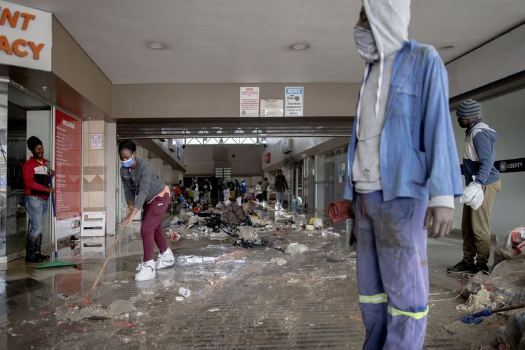Vrijwilligers helpen bij het opruimen van de ravage in de Bara Mall in Soweto. De veroordeling van de Zuid-Afrikaanse oud-president Jacob Zuma leidde tot grootschalige rellen en plunderingen. Beeld AFP