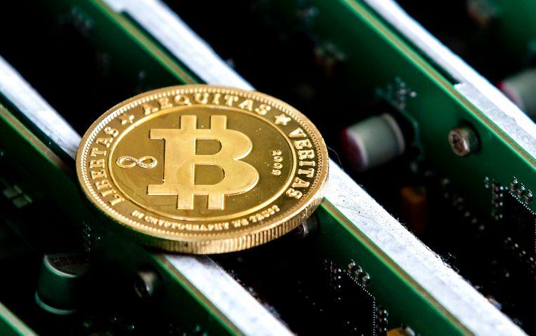Een munt met daarop het bitcoinlogo op het kantoor van Bitonic, een bedrijf dat euro's omwisselt in bitcoins of andere cryptovaluta.  Beeld ANP, Remko de Waal