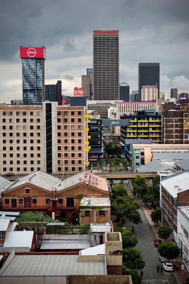 De binnenstad van Johannesburg gezien vanaf een flatgebouw in de wijk Maboneng. Achter het viaduct ligt de nieuwe wijk Jewel City, het voormalige Diamant Centre. Linksachter verrijst de woontoren die voorheen het hoofdkantoor van Absa was. Beeld Bram Lammers