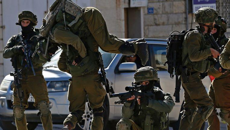 Een Israëlische soldaat met een gewonde collega op zijn rug. Beeld AFP