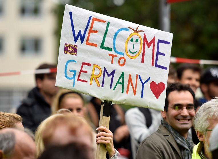Vluchtelingen die zondag aankwamen in Dortmund werden verwelkomd met borden waarop 'welkom in Duitsland' stond. Beeld AP