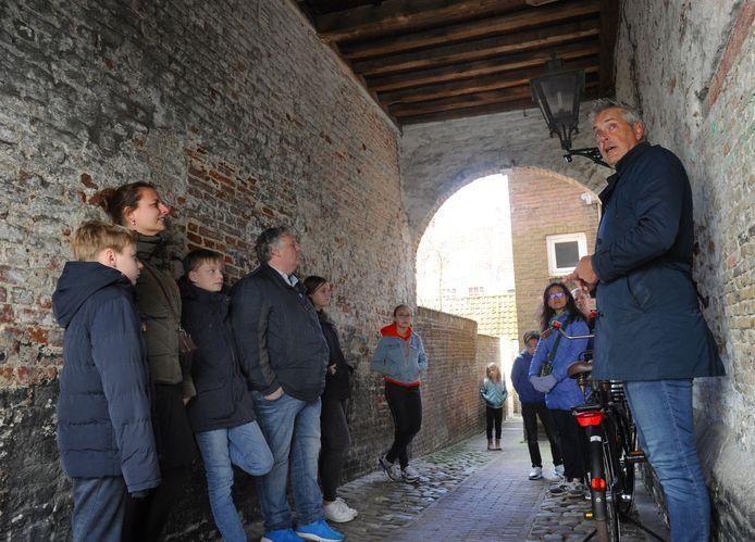 Hans Notebaart (rechts) met toeristen onder een van de poortjes die Middelburg rijk is.
