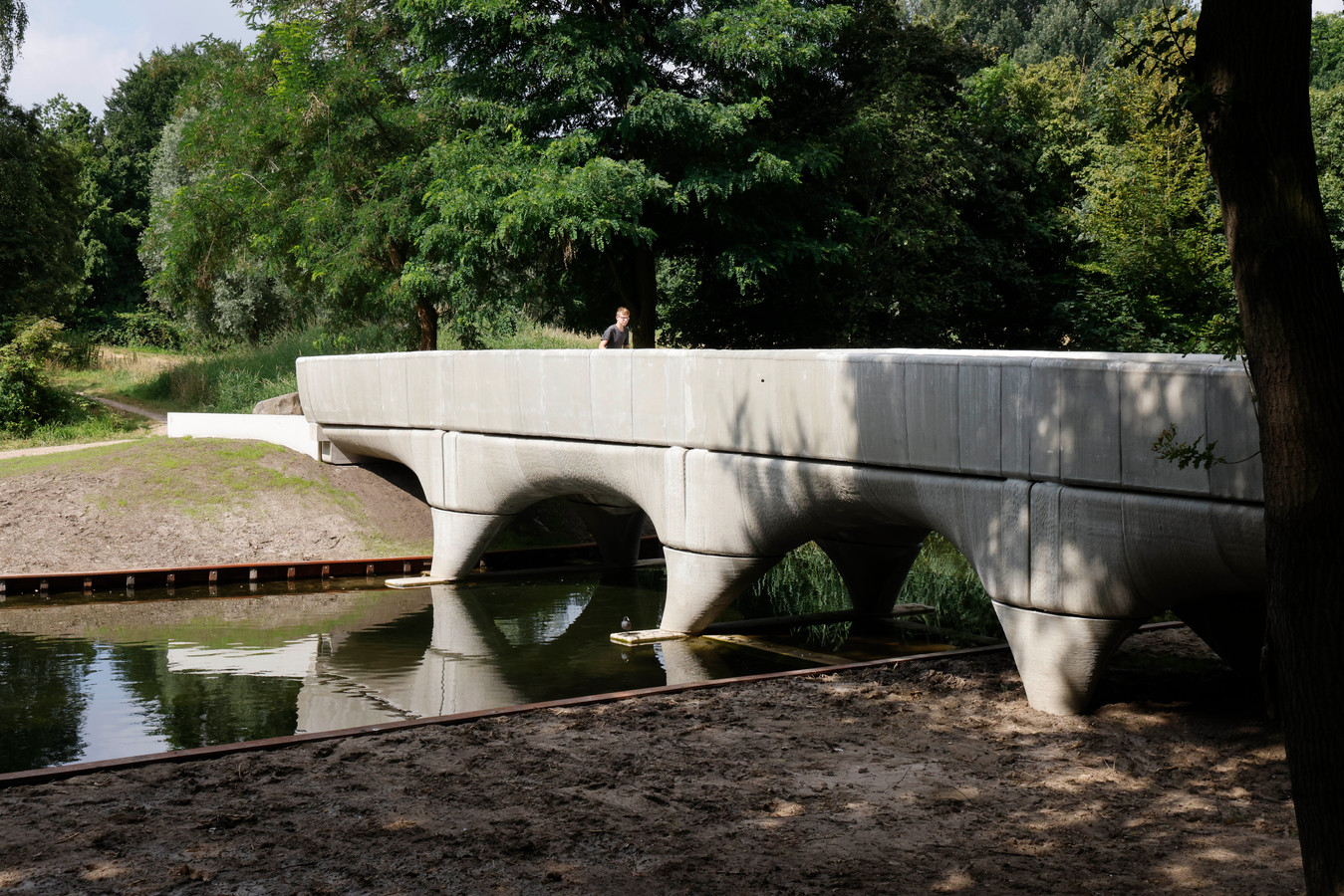 Een fietser gaat over de nieuwe brug in Zwanenveld. De betonnen brug is gemaakt met een 3D-printer.